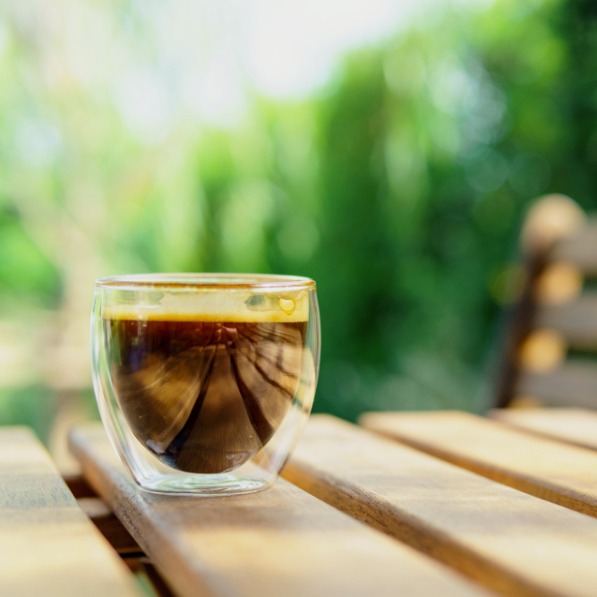 espresso coffee in transparent cup on the wooden table and chair in the garden. coffee, relax, holiday, feel good or thinker concept.